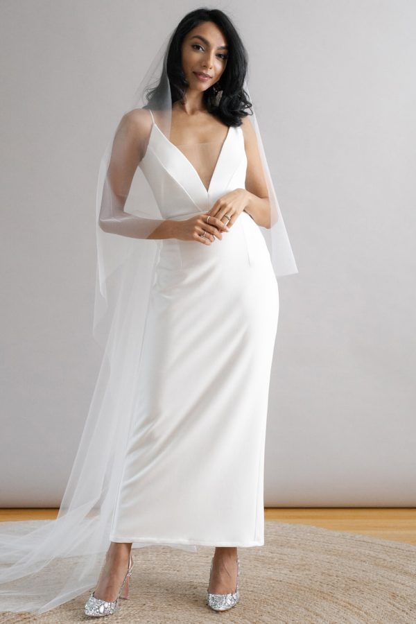 Minimalist ankle length wedding gown with low v-neck, thin straps and column skirt.