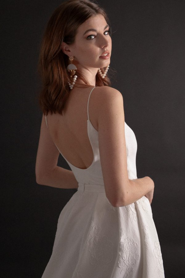 Low back, thin strap stretch crepe bodysuit with jacquard box pleat skirt.