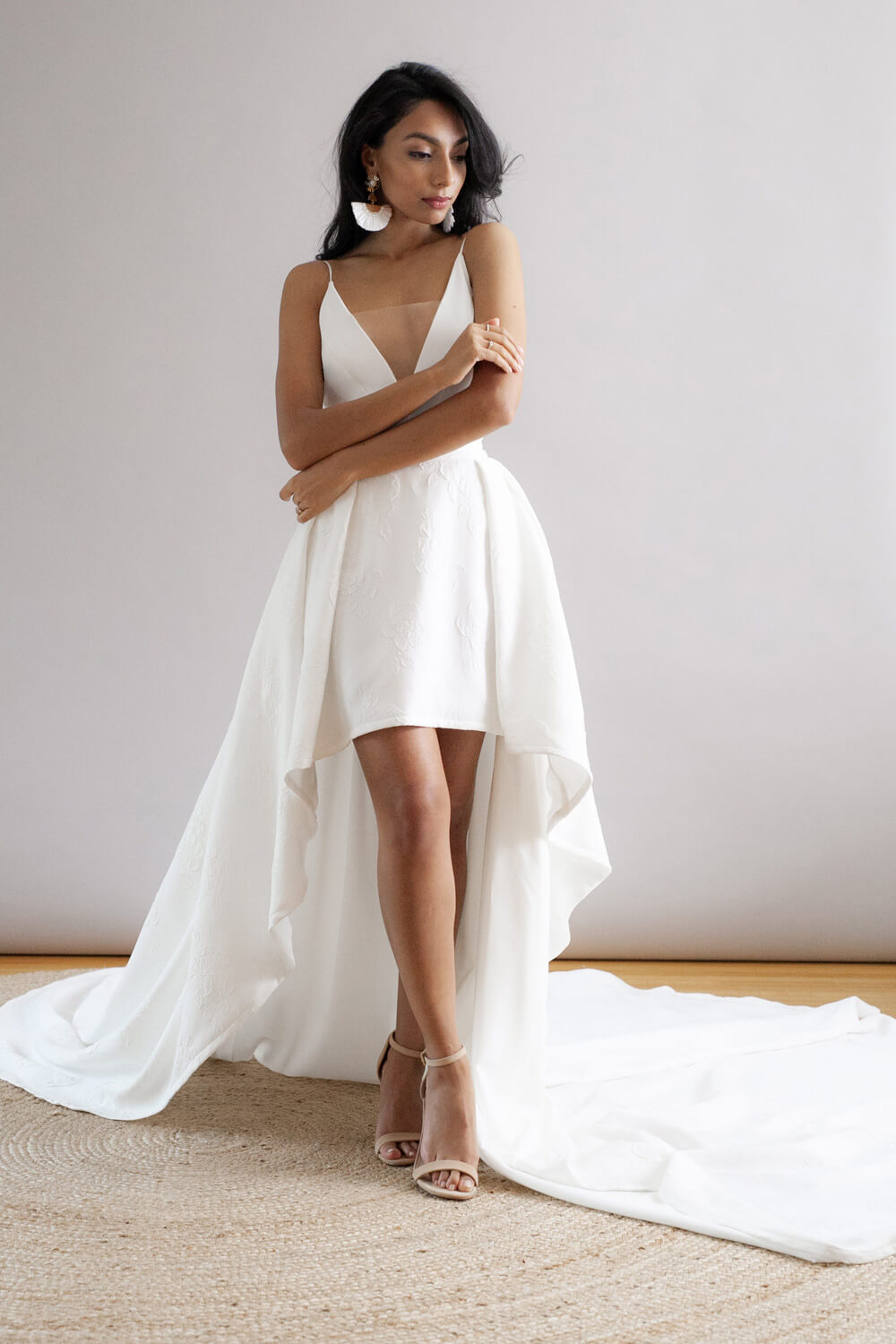 White dress with plunging v-neck, low back, spaghetti straps, and box-pleat hi-low skirt.