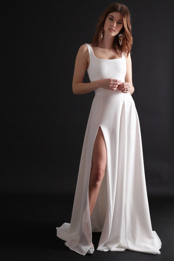 Dress with low, square neckline, shoulder straps, full a-line skirt and thigh-high slit.