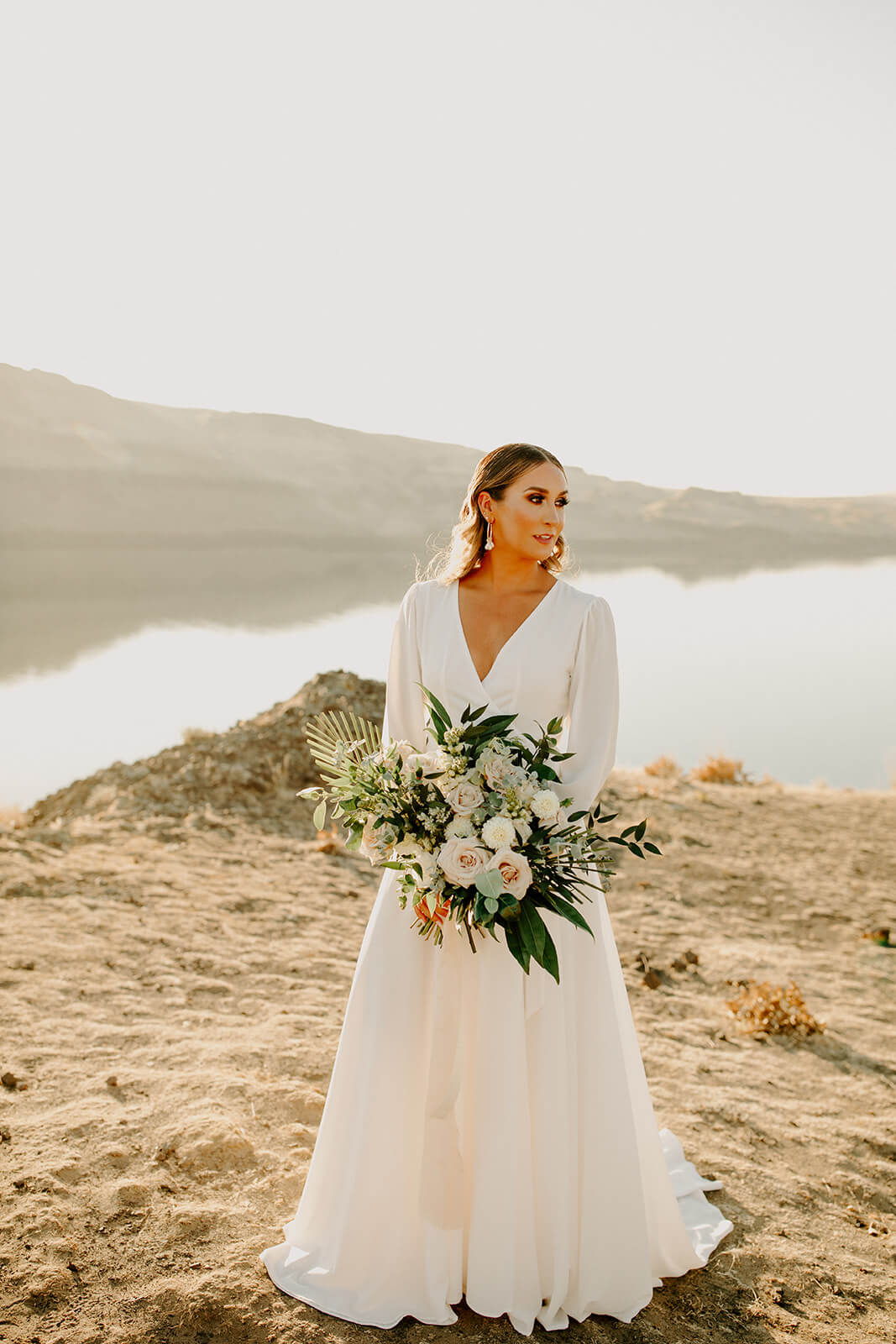 A bride wearing a flowing white dress in the desert